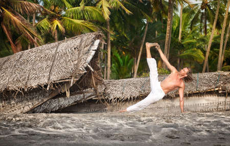 Yoga vasisthasana side plank pose by fit man in white trousers on the beach near the fishermen boats in Varkala, Kerala, India photo
