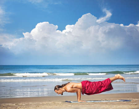 Yoga Mayurasana peacock handstand balancing pose by man with long hair in red trousers on the beach at ocean background  photo