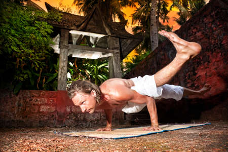 pada: Yoga eka pada koundinyasana pose by man in white trousers near stone temple at sunset background in tropical forest  Stock Photo