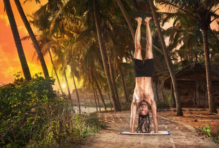 Yoga Adho Mukha Vrksasana handstand pose by fit man with dreadlocks on the beach near the fishermen hut in Varkala, Kerala, India