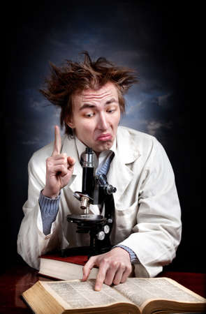 scientists: Funny young professor in white coat with microscope and books pointing up