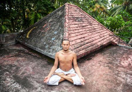 dhyana: Meditazione Yoga in posizione del loto da uomo in pantaloni bianchi sul tetto in Varkala, Kerala, India