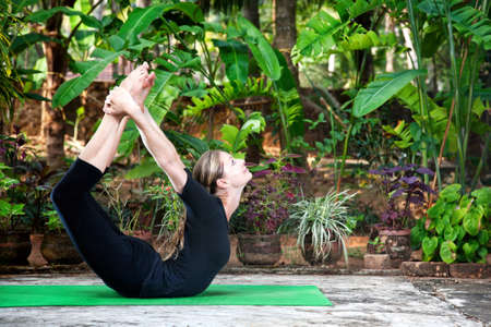 mat: Yoga Dhanurasana bow pose by woman in black cloth in the garden with palms, banana trees and plants in the pots
