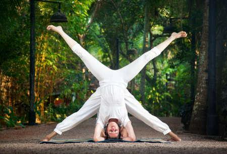 Yoga shirshasana Upavishtha Konasana head stand pose with spread legs by woman and man in white cloth in the garden photo