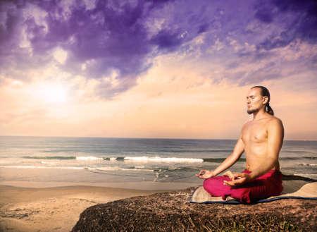 La meditación del yoga en posición de loto por el hombre con el pelo largo en los pantalones rojos en el acantilado cerca del océano en Varkala, Kerala, India