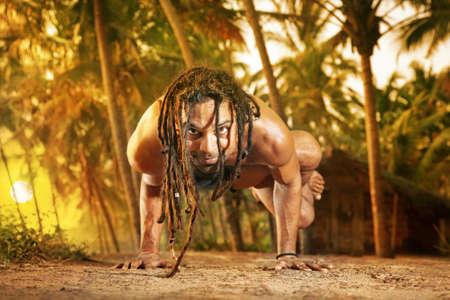 india fisherman: Yoga handstand pose by fit man with dreadlocks on the road near the fishermen hut in Varkala, Kerala, India Stock Photo