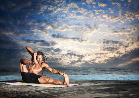 Yoga akarna dhanurasana archer pose by fit man with dreadlocks on the beach in the evening at ocean background photo