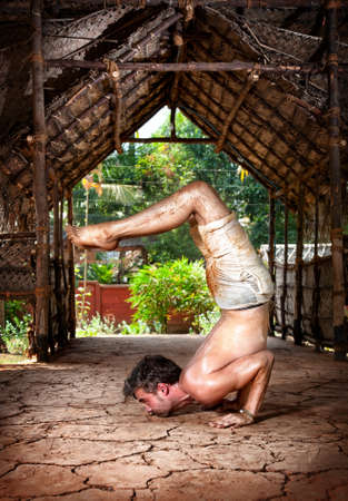 formidable: Yoga Ganda, Bherundasana Formidable Face pose by fit man in white trousers on the drought earth in yoga shala, Varkala, Kerala, India