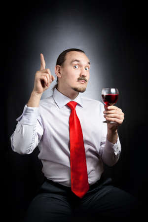 Businessman in red tie with funny mustache holding the glass of red wine and pointing up at black background photo