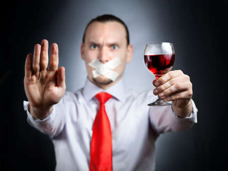 Businessman with plaster on his mouth in red tie holding the glass of red wine and gesturing stop sign by his palm at black background. Represents outcry alcoholic dependency photo