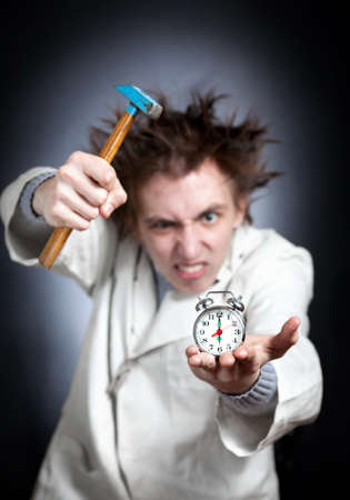 Crazy young student in white coat trying to break his alarm clock with his hammer which shows six am photo