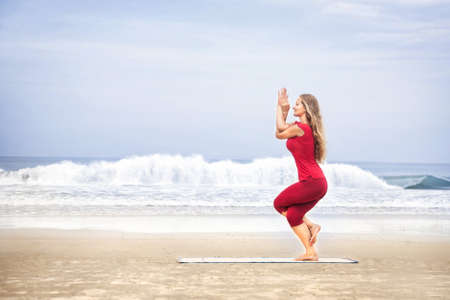 female pose: Yoga Garudasana eagle pose by young woman with long hair in red cloth on the beach at ocean background  Stock Photo