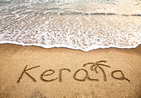 Kerala title on the sand beach near the ocean photo