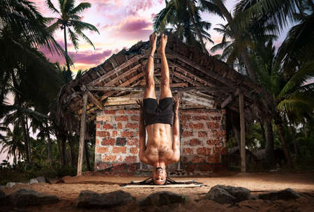 headstand: Yoga niralamba shirshasana, head stand pose without hands by fit man with dreadlocks on the beach near the fishermen hut in Varkala, Kerala, India