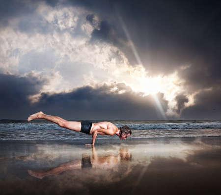 Yoga Mayurasana peacock handstand balancing pose by fit man on the beach near the ocean at dramatic sunset sky Stock Photo - 13488964