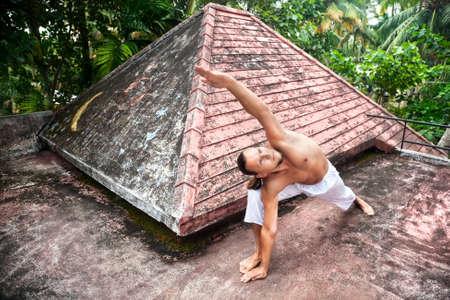 trikonasana: Yoga utthita parshvakonasana horizon pose by man in white trousers on the roof in Varkala, Kerala, India Stock Photo