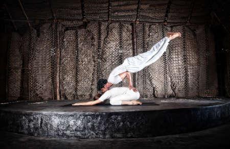 Couple yoga of woman doing vajrasana forward bending and man doing mayurasana on her back in white cloth in yoga hall, Varkala, Kerala, India Stock Photo - 13488963