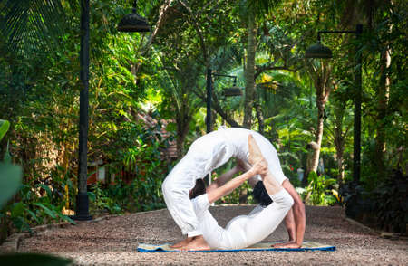 dhanurasana: Couple Yoga of man doing chakrasana and woman doing dhanurasana poses in white cloth in the garden. Represents yin and yang Stock Photo