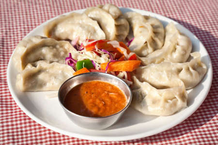nepali: Nepalese traditional dumpling momos served with tomato chatni and fresh salad in restaurant