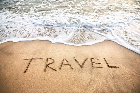 Travel word on the sand beach near the ocean photo