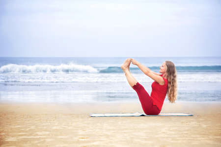 Yoga naukasana boat pose by young woman with long hair in red cloth on the beach at ocean background  photo