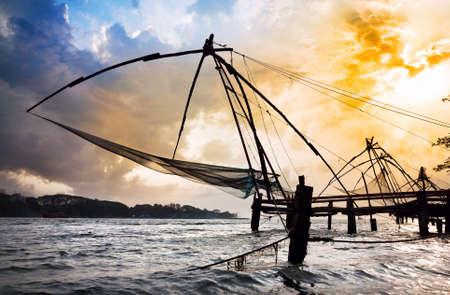 chinese fishing nets: Chinese Fishing nets at dramatic sunset sky background on Vypeen Island in Kochi, Kerala, India