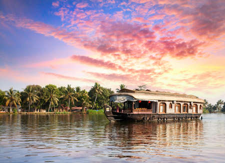 kerala culture: House boat in backwaters near palms at dramatic sunset sky in alappuzha, Kerala, India Stock Photo