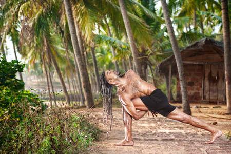 Yoga Baddha Parivrtta Parsvakonasana Revolved side angle pose by fit man with dreadlocks on the beach near the fishermen hut in Varkala, Kerala, India photo