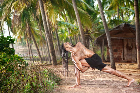 baddha: Yoga Baddha Parivrtta Parsvakonasana Revolved side angle pose by fit man with dreadlocks on the beach near the fishermen hut in Varkala, Kerala, India