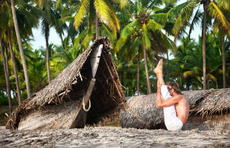 Yoga urdhva mukha paschimottanasana pose by fit man in white trousers on the beach near the fishermen boats in Varkala, Kerala, India photo