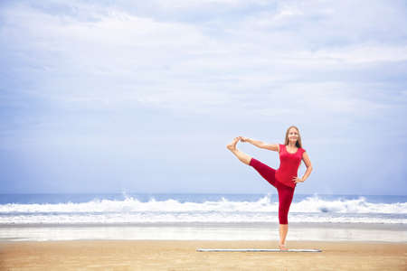 utthita: Yoga utthita Hasta Padangustasana one leg balance pose by young woman with long hair in red cloth on the beach at ocean background  Stock Photo