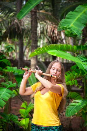 Beautiful girl in yellow shirt playing Indian traditional bamboo flute in banana and palm tree forest Varkala, Kerala, India photo