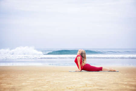 bhujangasana: Yoga bhujangasana cobra pose by young woman with long hair in red cloth on the beach at ocean background