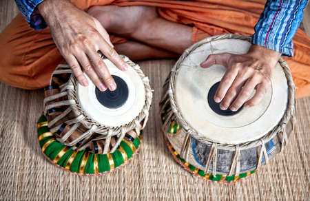 musical instruments: Man playing on traditional Indian tabla drums close up