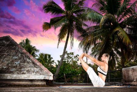 tissu blanc: Yoga Naukasana bateau pose par femme en tissu blanc sur le toit au fond de palmiers et de coucher de soleil � Varkala, Kerala, en Inde