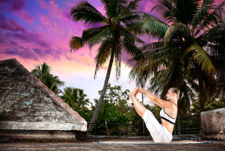 ashtanga: Yoga naukasana boat pose by woman in white cloth on the roof at palm trees and sunset background in Varkala, Kerala, India Stock Photo