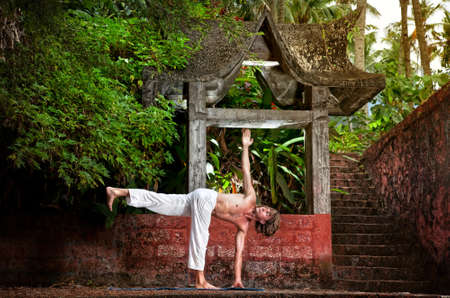 chandrasana: Yoga parivrtta ardha chandrasana revolved half moon pose by man in white trousers near stone temple at sunset background in tropical forest