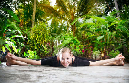 Yoga upavistha konaasana pose by woman in black cloth in the garden with palms, banana trees and plants in the pots photo