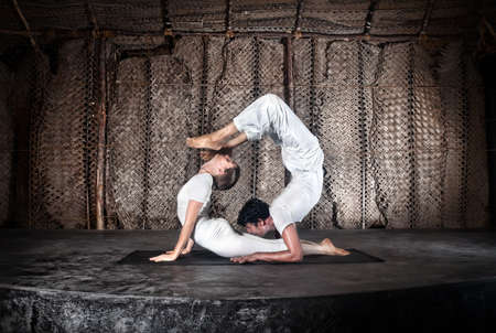 bhujangasana: Couple yoga of woman doing bhujangasana cobra pose and man doing Vrschikasana scorpion pose in white cloth in yoga hall, Varkala, Kerala, India