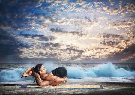 dwi: Yoga nidrasana yogic sleep pose by fit man with dreadlocks on the beach at ocean and sunset background