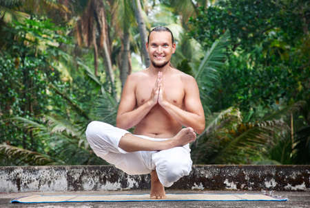 male palm: Yoga Ardha Baddha Padma Padangusthasana balancing on toes by man with beard in white trousers on the roof at palms background