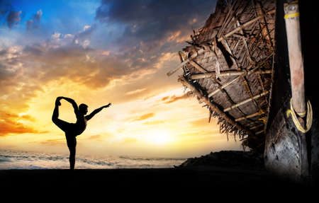 guru: man silhouette doing natarajasana dancer pose on the beach near the fisherman boat at sunset background in Varkala, Kerala, India