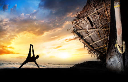 india fisherman: man silhouette doing vasisthasana side plank pose on the beach near the fisherman boat at sunset background in Varkala, Kerala, India Stock Photo