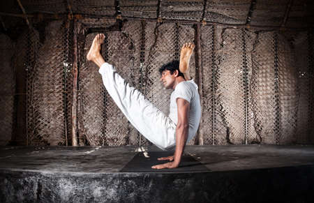 Yoga chakorasana pose by Indian man in white cloth in yoga shala, Varkala, Kerala, India photo