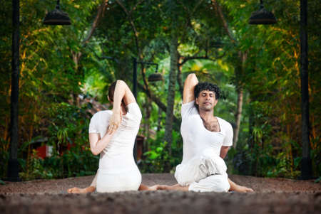 ashtanga: Couple Yoga of man and woman doing gomukhasana cow face pose front and back sides in white cloth in the garden Stock Photo