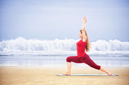 ashtanga: Yoga virabhadrasana I warrior pose by young woman with long hair in red cloth on the beach at ocean background  Stock Photo