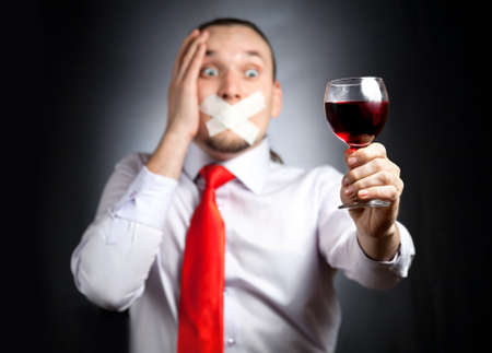 represents: Despair Businessman with plaster on his mouth in red tie holding the glass of red wine and at black background. Represents outcry alcoholic dependency