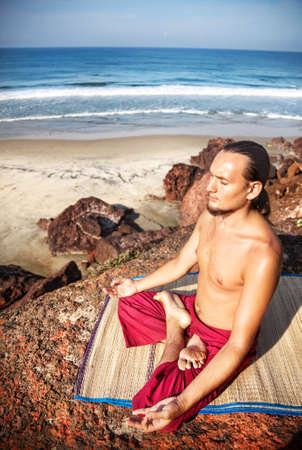 dhyana: Yoga meditation in lotus pose by man with long hair in red trousers on the cliff near the ocean in Varkala, Kerala, India