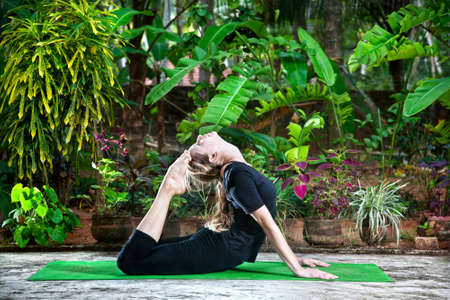 Yoga Raja Kapotasana backward bending pose by woman in black cloth in the garden with palms, banana trees and plants in the pots photo