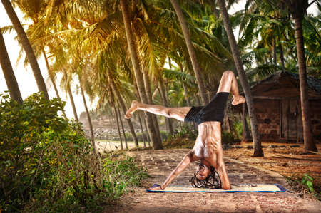 Yoga handstand pose by fit man with dreadlocks on the beach near the fishermen hut in Varkala, Kerala, India photo